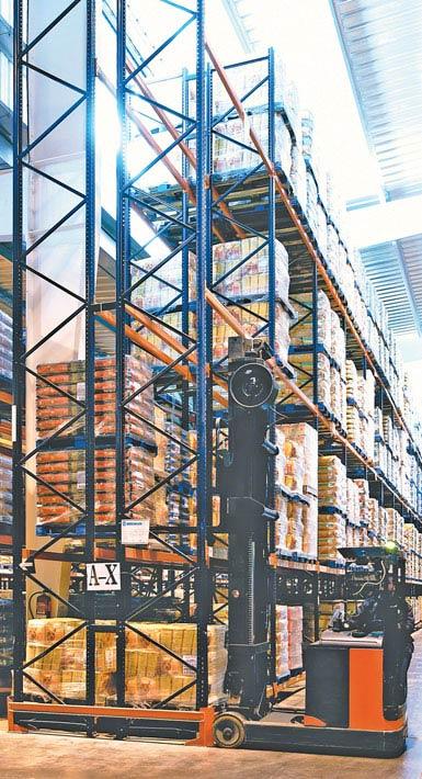 Zdjęcie wózka widłowego wysokiego składowania do regałów o podwójnej głębokości stosowanego w magazynie produktów spożywczych dużej konsumpcji